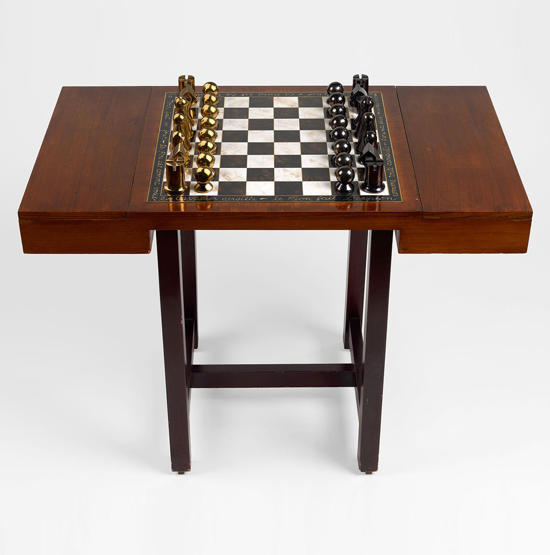 Chess Set and Table Chess set comprising thirty-two bronze pieces, sixteen patinated in black and sixteen patinated in gold, with an enamel and metal inlay board set on a wood tabletop with lidded storage compartments for the chess pieces. Designed in 1962 and executed between 1962 and 1966 in an edition of 50 plus 5 artist's proofs (Marcel Zerbib, Paris). Inscribed Man Ray and numbered 21/50 (on the white king); inlaid with the artist's poem in French in his handwriting (around the perimeter of board). King: height 10 cm. Tabletop: width 57.1 cm; length 99.1 cm; height 9.9 cm. Provenance: Personal collection of Arturo Schwarz, Milan (acquired from the artist in 1964). Chess Set and Table Chess set comprising thirty-two bronze pieces, sixteen patinated in black and sixteen patinated in gold, with an enamel and metal inlay board set on a wood tabletop with lidded storage compartments for the chess pieces. Designed in 1962 and executed between 1962 and 1966 in an edition of 50 plus 5 artist's proofs (Marcel Zerbib, Paris). Inscribed Man Ray and numbered 21/50 (on the white king); inlaid with the artist's poem in French in his handwriting (around the perimeter of board). King: height 10 cm. Tabletop: width 57.1 cm; length 99.1 cm; height 9.9 cm. Provenance: Personal collection of Arturo Schwarz, Milan (acquired from the artist in 1964).